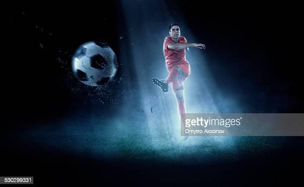 Football joueur frappe de balle dans spotlight