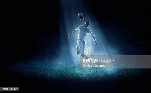 Soccer player kicking ball in spotlight