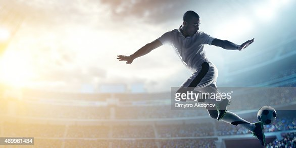 Soccer player kicking ball in stadium
