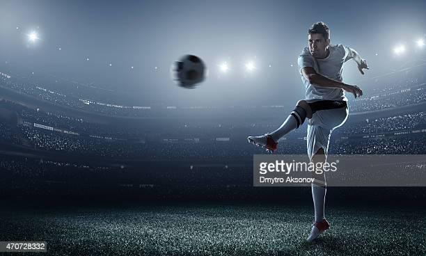 Soccer player kicking ball in stadium