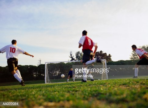 soccer player kicking ball into goal stock photo getty