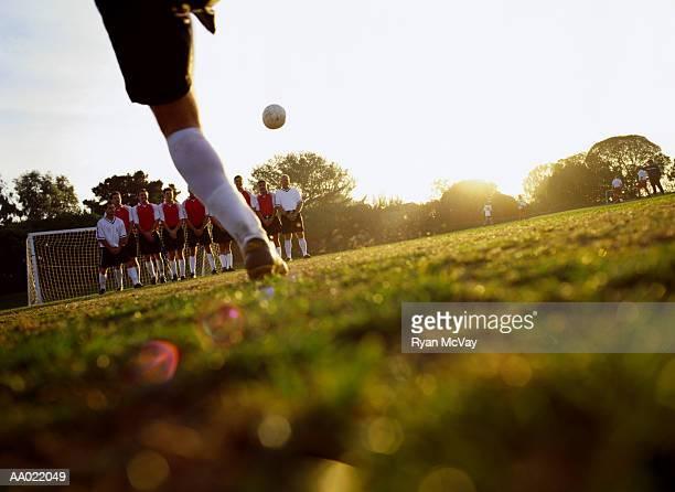Soccer player kicking ball towards goal, ground view