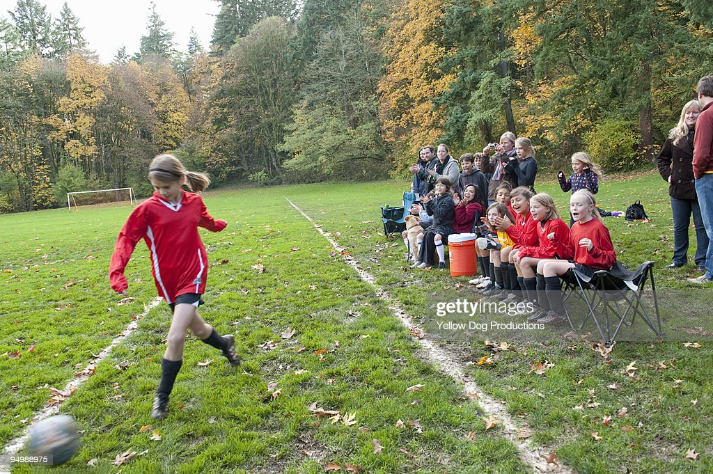 Soccer player kicking ball while spectators cheer : Stock Photo