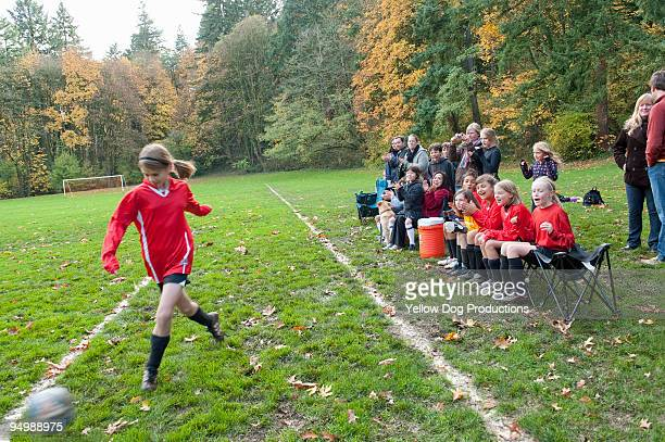 Soccer player kicking ball while spectators cheer