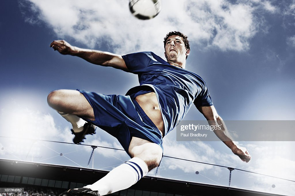 Soccer player kicking soccer ball : Stock Photo