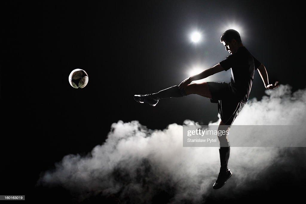 Soccer player kicking the ball at night on stadium : Stock Photo