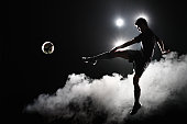 Soccer player kicking the ball at night on stadium