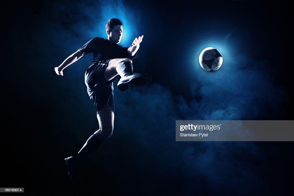 Soccer player kicking the ball at night
