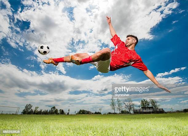 Jugador de fútbol coleando la pelota mientras que a mediados de aire.