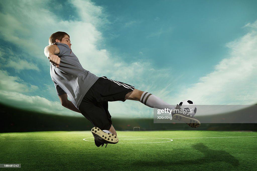 Soccer player kicking the soccer ball in mid air, in the stadium with the sky