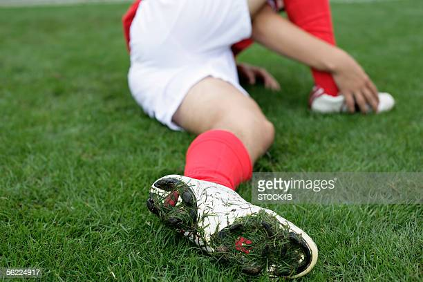 Soccer player lying injured on the grass