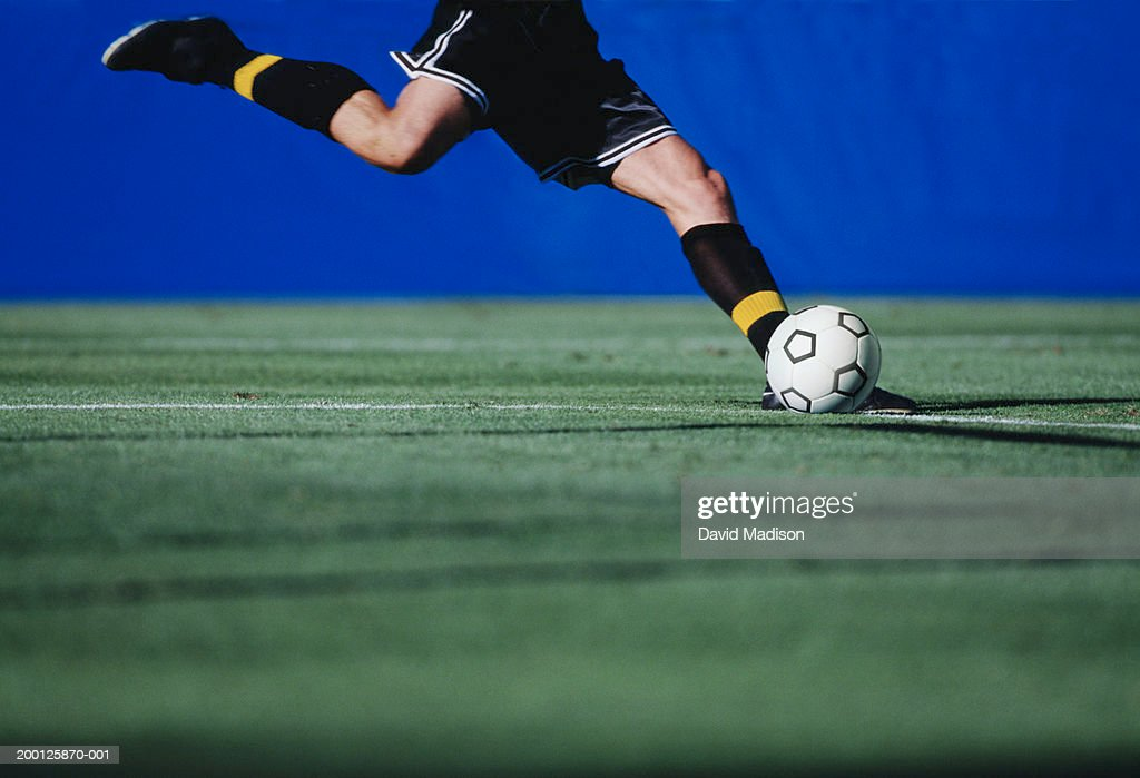 Soccer player on field preparing to kick ball, low section : Stock Photo