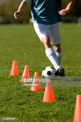 Soccer player perfoms training with a football