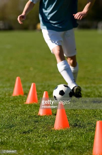 Jogador de futebol com uma bola de futebol de treino Efectue