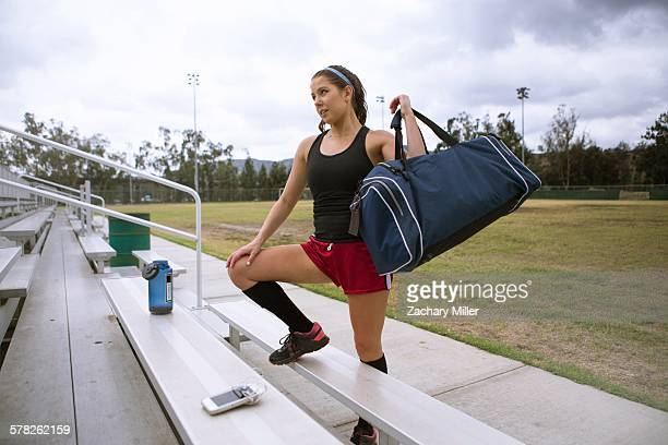 Soccer player placing sports bag on bench