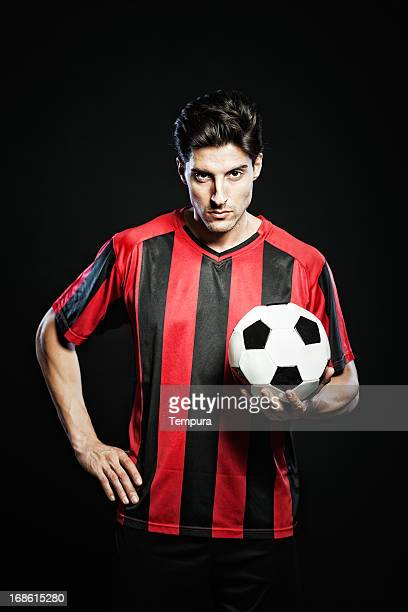 Soccer player portrait on black background, vertical.