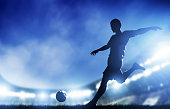 A soccer player shrouded in blue light has his arms raised to his shoulders.  His foot is poised to kick the soccer ball and make a goal.