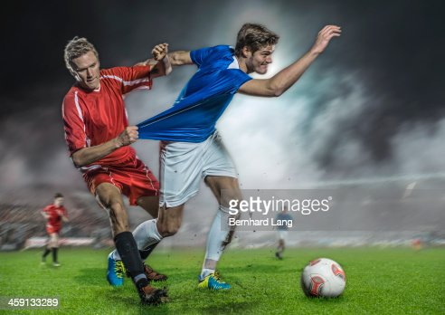 Soccer player pulling jersey of his opponent