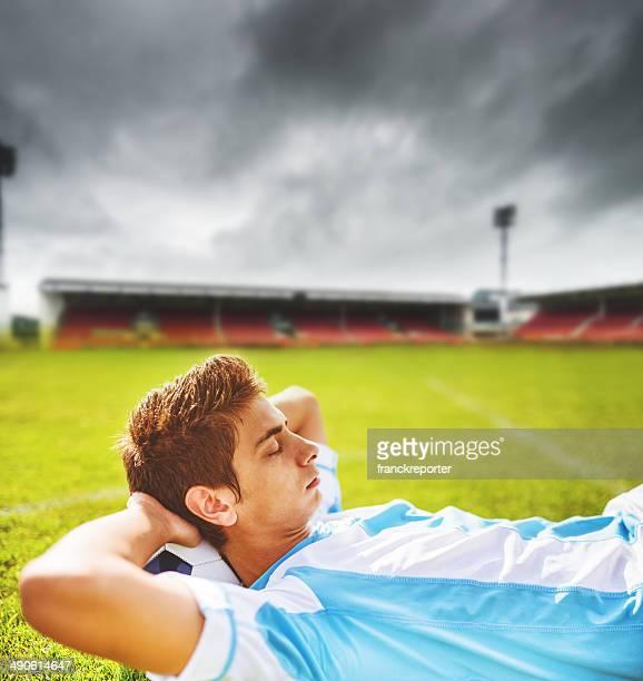 Calciatore rilassante sul campo