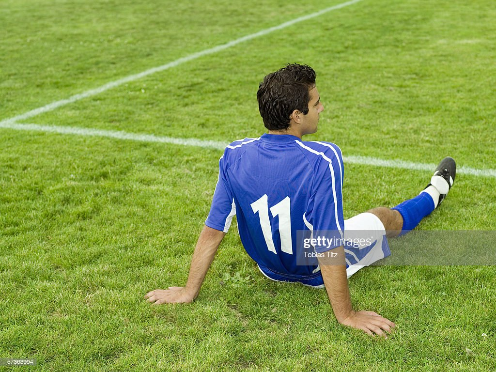 A soccer player resting on the sidelines