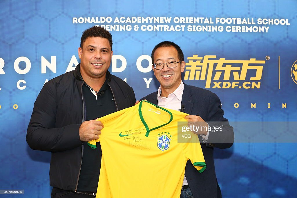 Soccer player Ronaldo (L) and Yu Minhong, founder and chairman of New Oriental Education and Technology Group, attend the opening and contract signing ceremony of Ronaldo Academy-New Oriental Football School on November 17, 2015 in Beijing, China. Brazilian soccer player <a gi-track='captionPersonalityLinkClicked' href=/galleries/search?phrase=Ronaldo+Nazario+-+Soccer+Player&family=editorial&specificpeople=185240 ng-click='$event.stopPropagation()'>Ronaldo Nazario</a> cooperated with the New Oriental Education and Technology Group to open a football school on Tuesday in Beijing as he planned to open 30 football schools in China.