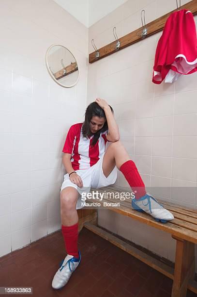 Soccer player sitting on bench