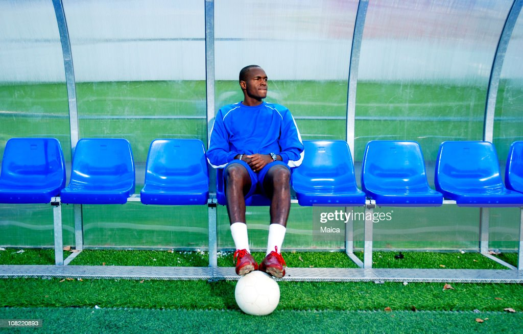 Soccer Player Sitting on Sidelines