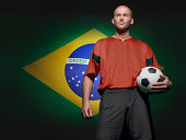Soccer player standing in front of Brazilian flag