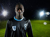 Soccer player standing on field in rainstorm
