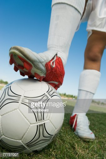 Soccer Player Standing with Cleats on Ball : Stock Photo