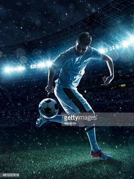 Soccer player tackling a ball on stadium