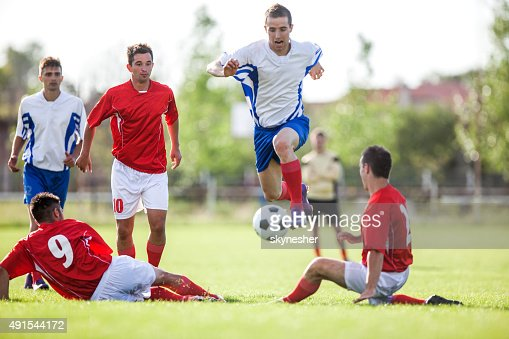 Soccer player trying to avoid his opponents during match.