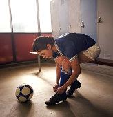 Soccer player tying cleats in locker room