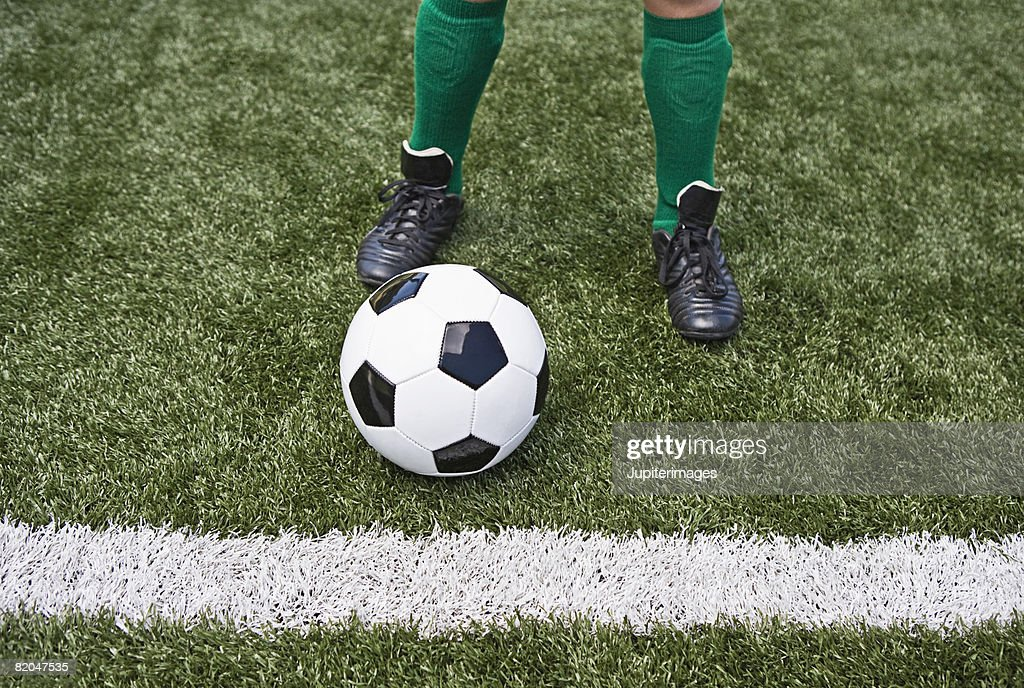 Soccer player with ball at half-way line : Stock Photo