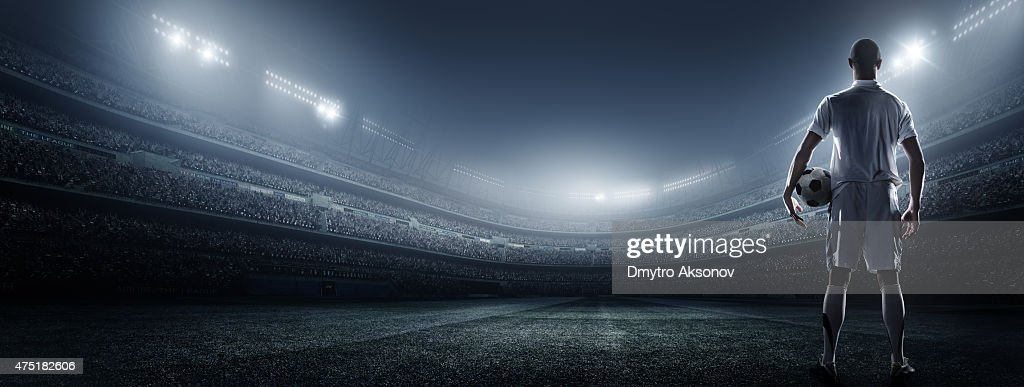 Soccer player with ball in stadium