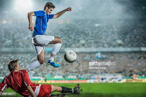 Soccer player with ball jumping over his opponent