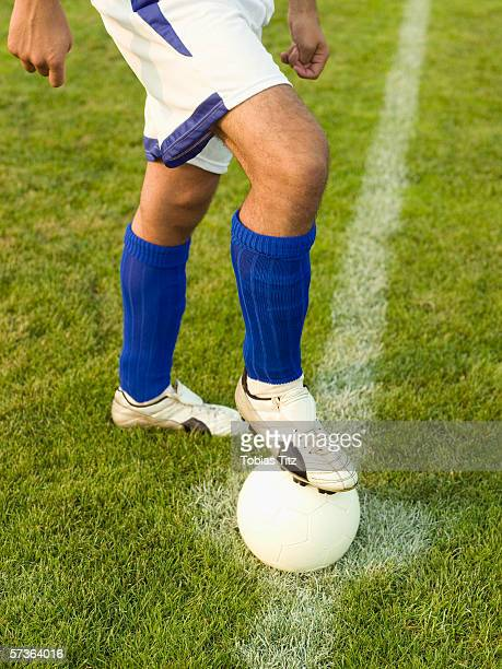 A soccer player with his foot on a soccer ball
