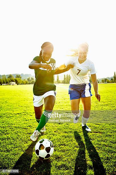 Soccer players challenging for ball during match