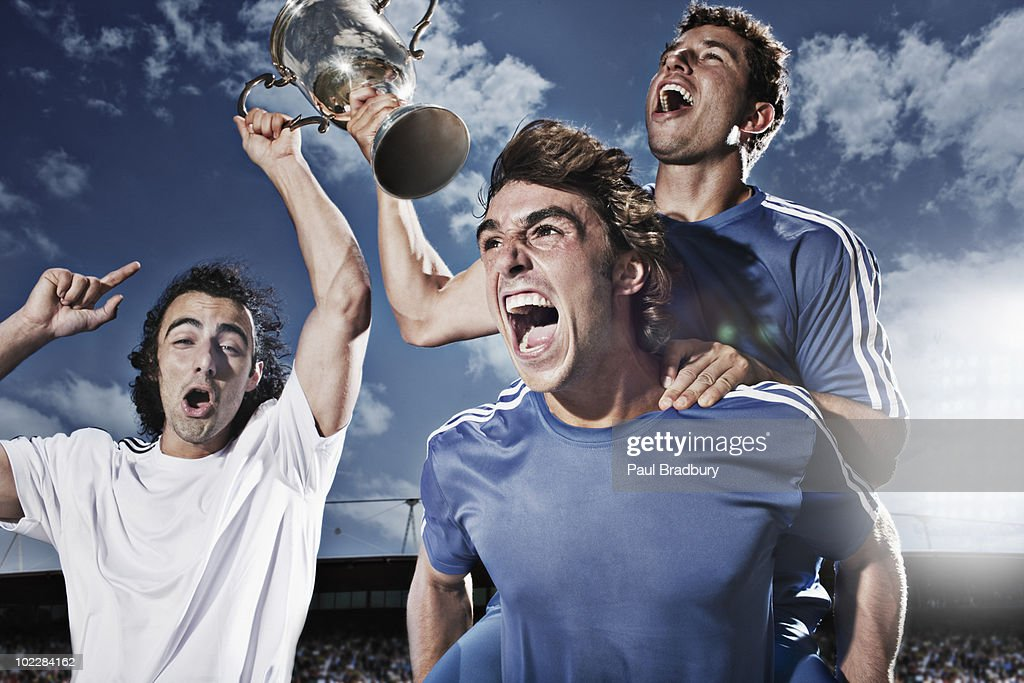 Soccer players cheering with trophy : Stock Photo
