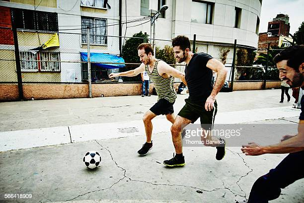 Soccer players converging on ball in urban park