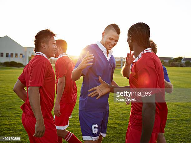 Soccer players greeting each other after game