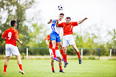 Soccer players in action at the soccer match. Two of them are jumping to head the ball.