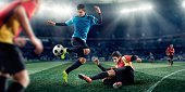 Close up image of professional soccer player jumping over tackling player during game in floodlit outdoor arena.