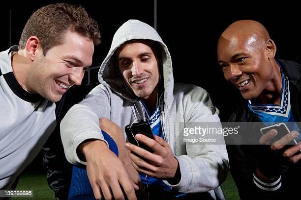 Fußball-Spieler, die im cellphone auf dem Spielfeld