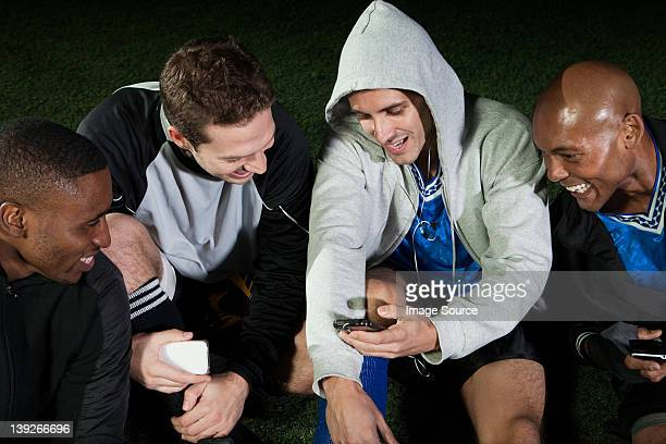 Soccer players looking at cellphone on pitch
