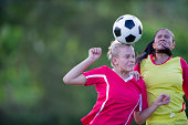 Two female soccer players competing for the ball.