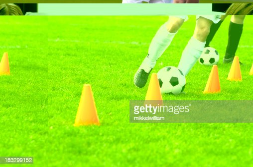 Soccer players run with football past cones during training session