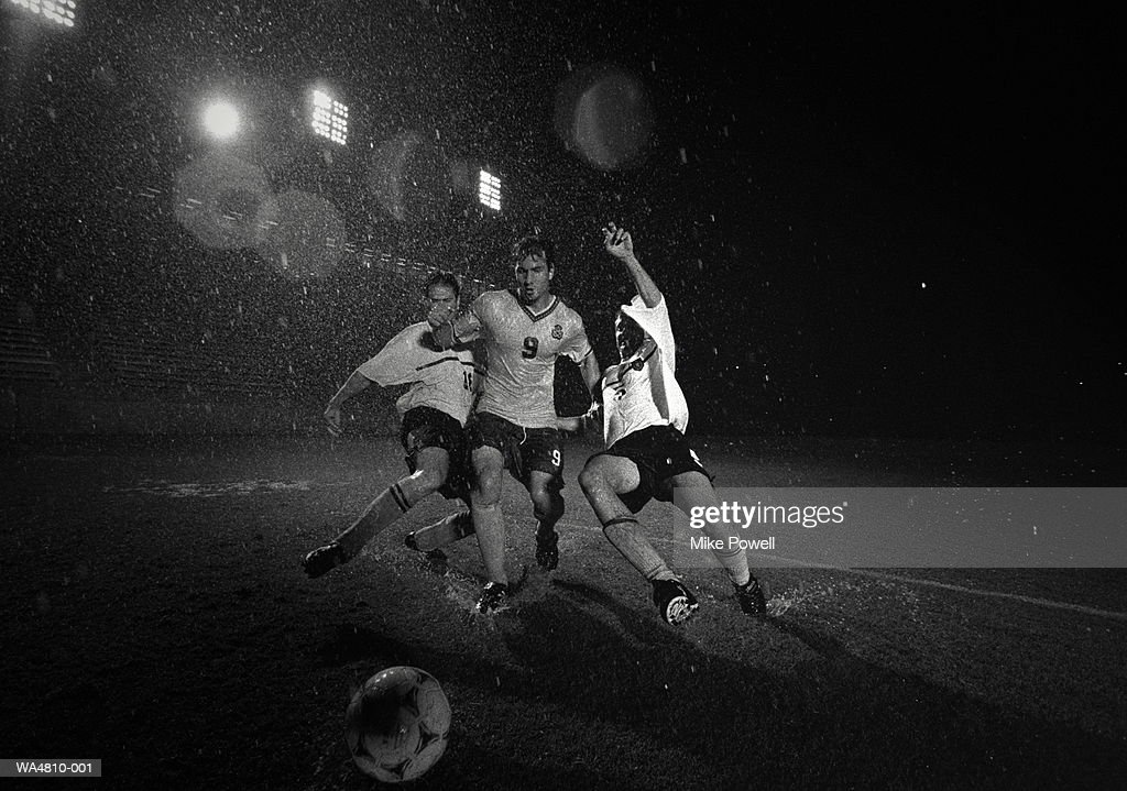 Soccer players running after ball : Stock Photo