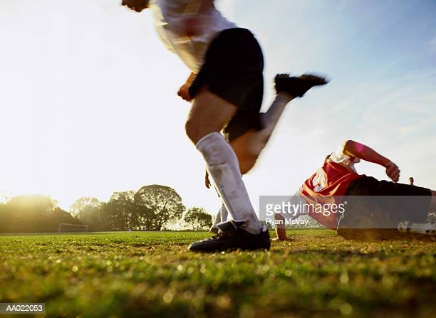 Soccer players running on pitch, low section (blurred motion)