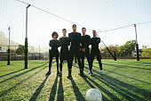 Full length of five a side football team on field during training. Soccer players standing together on football pitch.